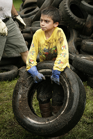 Child picking up tire